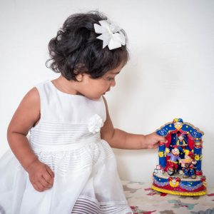 Indian girl toddler in white dress looks at Punch and Judy toy
