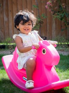 Indian girl toddler riding pink plastic horse in back garden