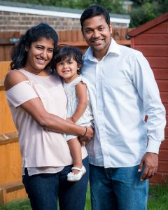 Indian mother, father and young daughter stand for photo in back garden
