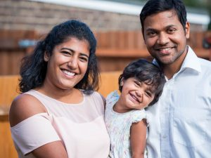 Indian mother, father and young daughter smiling in back garden