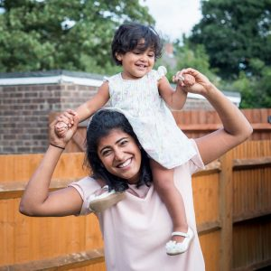 Indian mother with young daughter on shoulders in back garden
