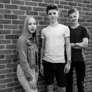 Teenage girl and two boys in front of brick wall