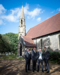 Groomsmen outside church with spire beneath blue sky