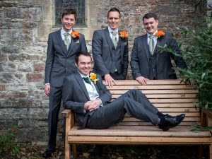 Groom reclines on bench as groomsmen stand behind him
