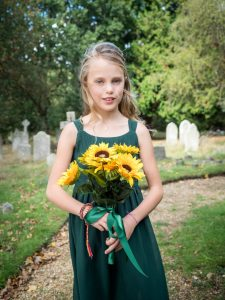 Young bridesmaid in churchyard holding sunflowers