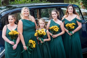Bridesmaids  in bottle green dresses next to wedding car