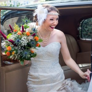 Bride smiles as she steps out of vintage wedding car