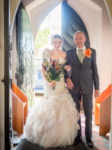 Bride and father backlit in cburch doorway