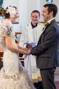Bride looks overjoyed as vicar and groom look smile back