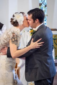 Newly-married couple kiss in church
