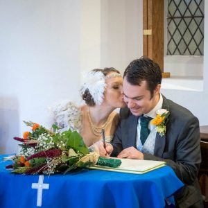 Bride kisses groom's cheek as he signs marriage register