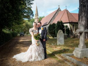 Bride and groom pose with church and vintage car in background