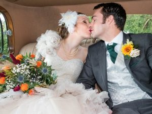 Bride and groom kiss in vintage wedding car