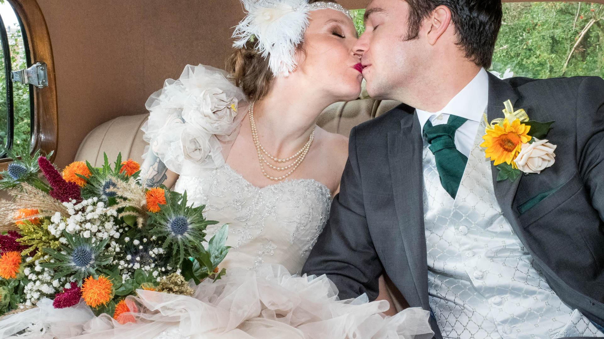 Bride and groom kiss in vintage wedding car