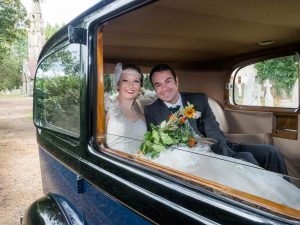 Bride and groom smiling in vintage wedding car