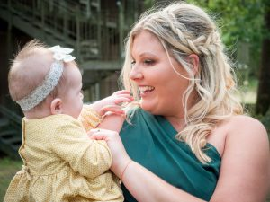 Bridesmaid in bottle-green dress cradles baby in her arms