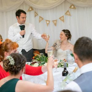 Groom clinks glasses with bride at Marwell Hotel wedding reception