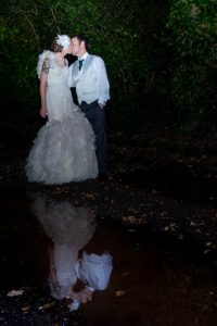 Bride and groom, reflected in a large puddle, kiss at night