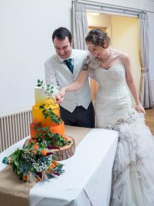 Bride and groom cut orange and white wedding cake