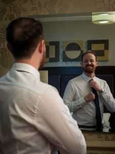 Bridegroom admires his apppearance in his hotel room mirror as he straightens his tie