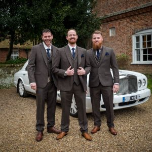 Bridegroom and his supporters in front of white Bentley wedding car