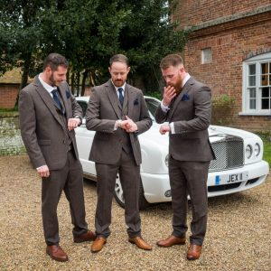 Bridegroom and his supporters check their watches in front of white Bentley wedding car