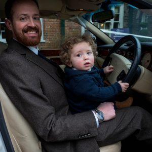Bridegroom and his young son in the driving seat of a Bentley wedding car