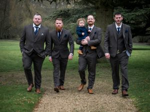 Bridegroom, his young son and supporters walk towards the camera outside at Norton Park