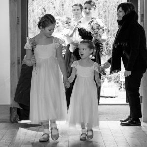 Two young bridesmaids enter the Tithe Barn at Norton Park at the start of a wedding