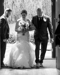A bride and her father enter the Tithe Barn at Norton Park at the start of her wedding