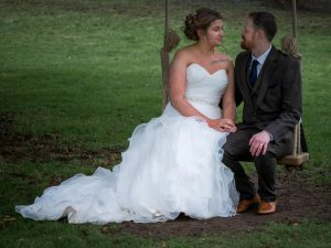 A bride and her new husband on a swing in the grounds at Norton Park