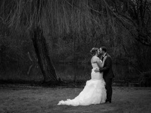 A bride and her new husband kiss in the grounds at Norton Park