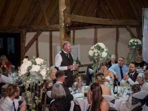 A father addresses the guests at his daugher's wedding in the Tithe Barn at Norton Park