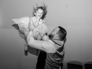 A wedding guest entertains his toddler daughter by throwing her in the air