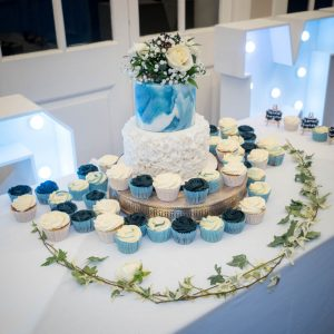 A wedding cake decorated with blue marble-effect icing surrounded by cup cakes