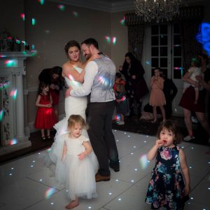 Joined by a couple of toddlers, a bride and her new husband enjoy their first dance at Norton Park