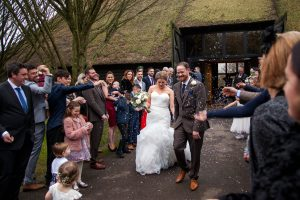 A bride and her new husband leave the Tithe Barn at Norton Park through a confetti shower