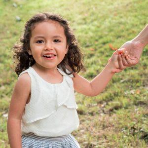 Little girl in garden holding mother's hand