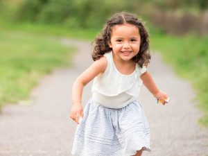 Little girl runs down gravel paths and smiles