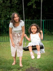 Little girl on swing with mother