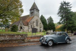 Bentley wedding limousine outside a an English country church in autumn