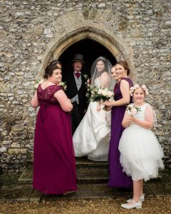 Bride, her father and bridesmaids wait to enter an English country church before her wedding