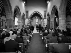 Bride and groom stand before the vicar in an English country church