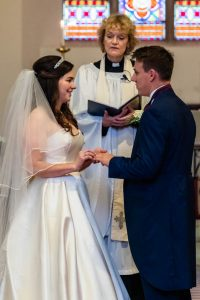 Bride says her wedding vows to her groom as the vicar looks on in an English country church