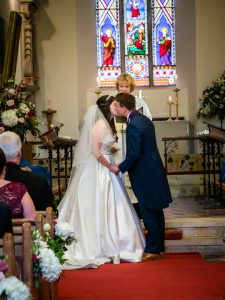 Bride and groom eschange their first kiss as man and wife in an English country church