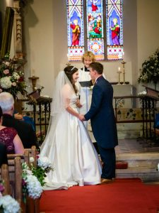 Bride and groom smile after their first kiss in an English country church