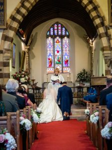 Bride and groom kneel at the altar for the blessing in an English country church