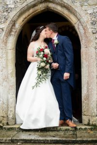 Bride and groom kiss n the doorway of an English country church