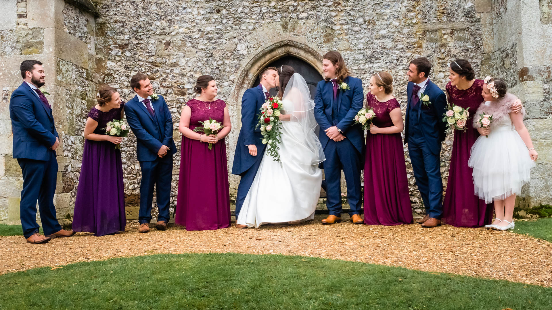 Guests look on as a bride and groom kiss outside an English country church