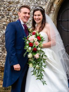 Bride and groom smile outside an English country church